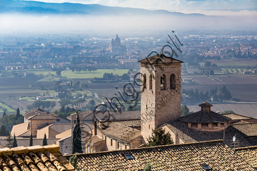Assisi:  view of rooves and the bell tower of the Abbey of St Peter. In the background, amont the fog, the dome of the Sanctuary of the Porziuncola.