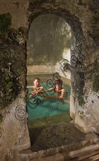 """Bormio, Spa,  the thermal baths """"Bagni Vecchi"""": a couple of guests in one of the pools of the Roman Baths."""