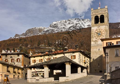 """Bormio, Historical Centre, Cavour or Kuerc Square. Here there are the Kuerc (low loggia with a slate roof where justice was administered and people's assemblies were held), the people's Tower with the """"Baiona"""" (big bell which was rung to to call the council of the region to meeting)."""