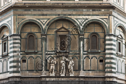 """Florence, the Baptistery of St. John, exterior, the Eastern   façade in Carrara white marble and green Prato marble:  detail of """"The Baptism of Christ"""" (copy of the original statues in the Opa Museum) by Andrea Sansovino, (1467-1529), Vincenzo Danti (1530-1576) and Giuseppe Spinazzi (1726-1798)."""