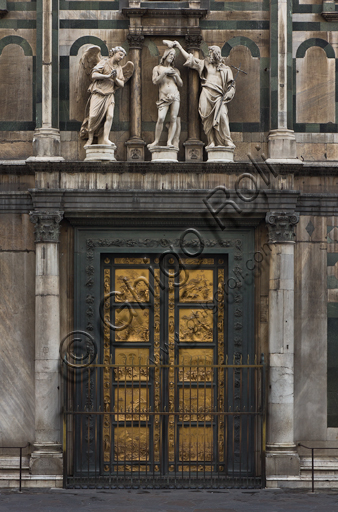 """Florence, the Baptistery of St. John, exterior, the Eastern   façade in Carrara white marble and green Prato marble:  detail of the Door of Paradise by Lorenzo Ghiberti and of """"The Baptism of Christ"""" (copy of the original statues in the Opa Museum) by Andrea Sansovino, (1467-1529), Vincenzo Danti (1530-1576) and Giuseppe Spinazzi (1726-1798)."""