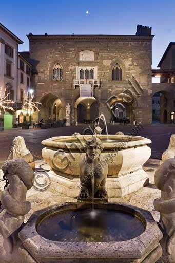 Bergamo, Città alta, Piazza Vecchia: night view of  the fountain given by the podesta Alvise II Contarini in 1780, and, in the background, Palazzo della Ragione (Ragione Palace).