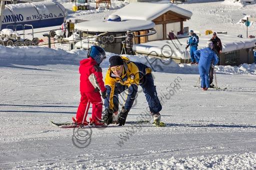 """Bormio 2000, Italian Ski School """"Gallo Cedrone"""": a ski teacher is giving a child a lesson"""