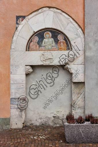 Bormio, Collegiata dei Santi Gervasio e Protasio (patroni di Bormio), facciata: portale laterale con lunetta affrescata (XV sec.).