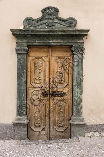 Bormio: porta in legno di antica casa con stipite in pietra.