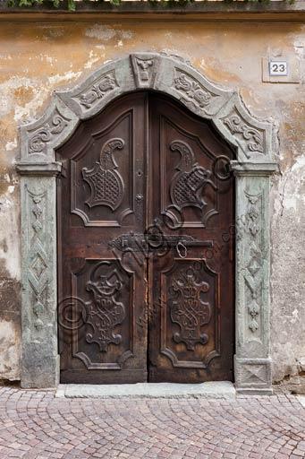 Bormio: old house wooden door with stone jamb.