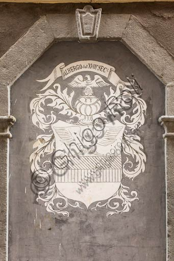 Bormio: emblem on the façade of a historic hotel in the centre.