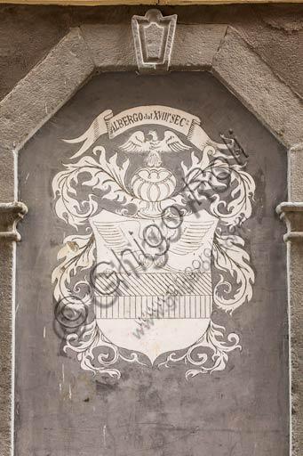 Bormio: stemma sulla facciata di un antico albergo del centro storico.