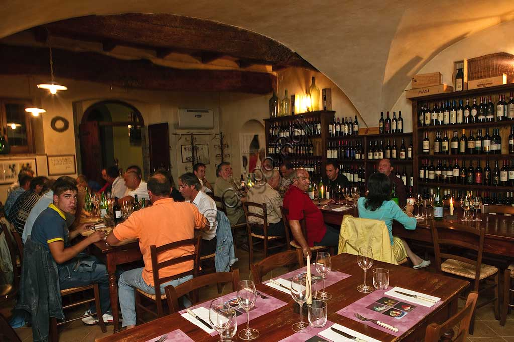 """Bevagna, the """"Bottega Di Piazza Onofri"""", wine shop and restaurant: shelves with bottles of red wine and customers having a meal at tables."""