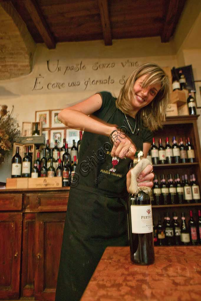 """Bevagna, the """"Bottega Di Piazza Onofri"""", wine shop and restaurant: a waitress uncorking a bottle of red wine."""