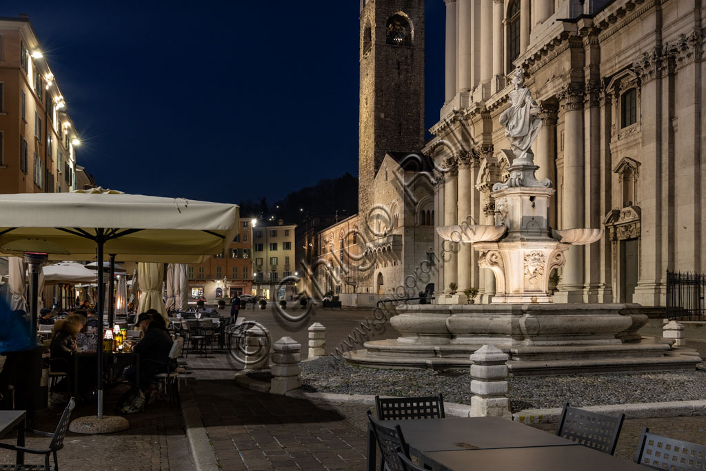 """Brescia, Paolo VI Square: night view. From the left, the Broletto with the Pégol Tower and the Loggia delle Grida; and part of the facade of the Duomo Nuovo  (the New Cathedral) , in late Baroque style with the facade of Botticino marble. In the foreground, the fountain with a copy of the neoclassical statue of Minerva, known as """"Armed Brescia""""."""