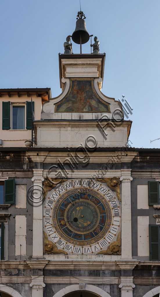 Brescia, piazza della Loggia (a Renaissance square where the Venetian influence is evident): the Clock Tower (1540 - 1550) with the astronomical quadrant with concentric rings, decorated in gold and blue and with symbols of the Zodiacal signs. Above the dial, a plinth adorned with the symbol of the sun and a volute base that stand as a pedestal for the automata, the popular Macc de le ure (crazy hours) that hammer at every hour on the bell.