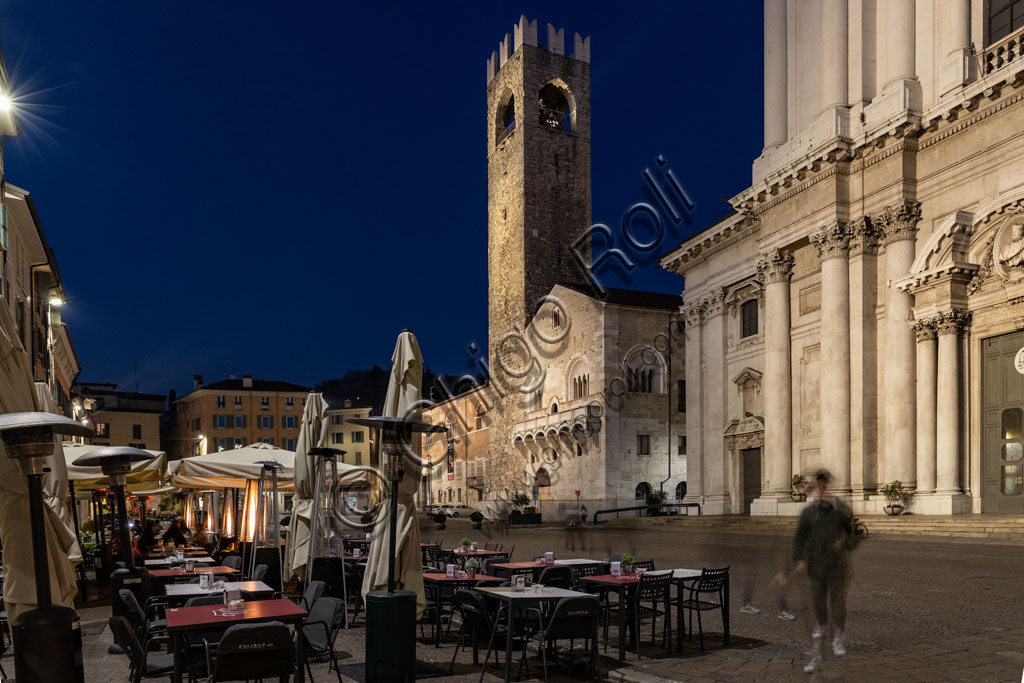 Brescia, Paolo VI Square: night view. From the left, the Broletto with the Pégol Tower and the Loggia delle Grida; and part of the facade of the Duomo Nuovo  (the New Cathedral) , in late Baroque style with the facade of Botticino marble.