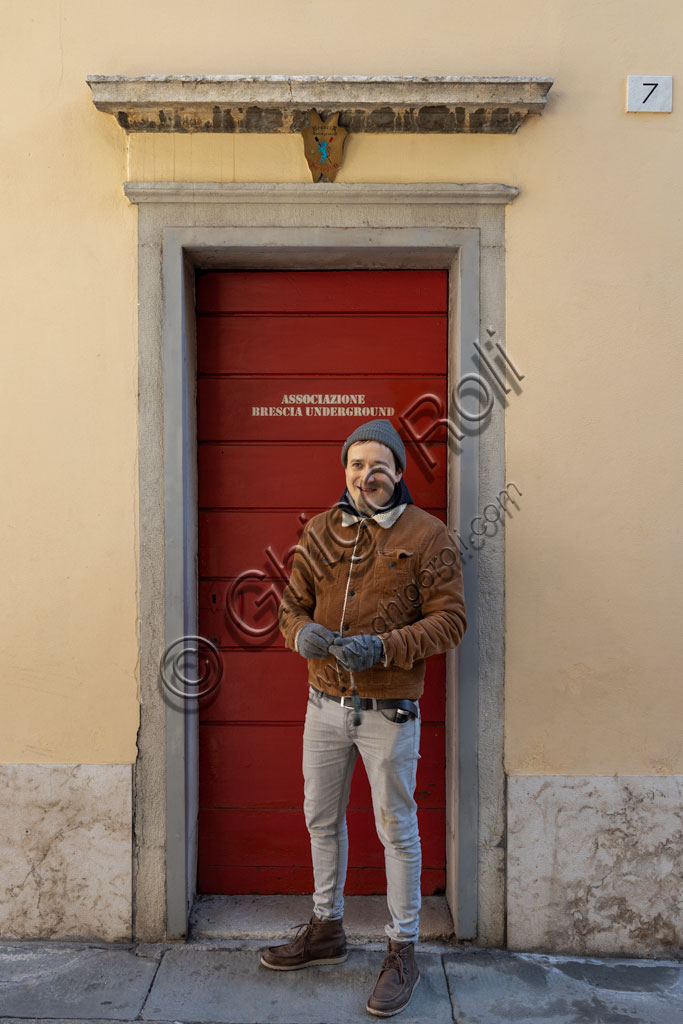 "Brescia. ""Brescia Underground"" Association: the president, Andrea Busi, in front of the ""Red Door"", the entrance to the Serraglio, one of the most important underground areas of the city."