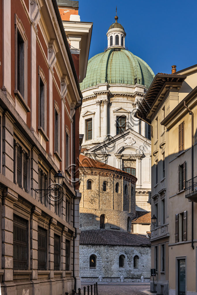 Brescia: alley of the historical centre. In the background, the dome of the New Cathedral, in late Baroque style and the cylindrical structure of the Old Cathedral, built at the end of the eleventh century.