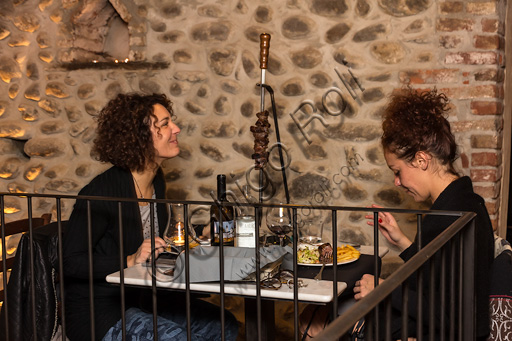 Candelo, Ricetto (fortified structure) Restaurant Il Torchio 1763:  two young customers having dinner.