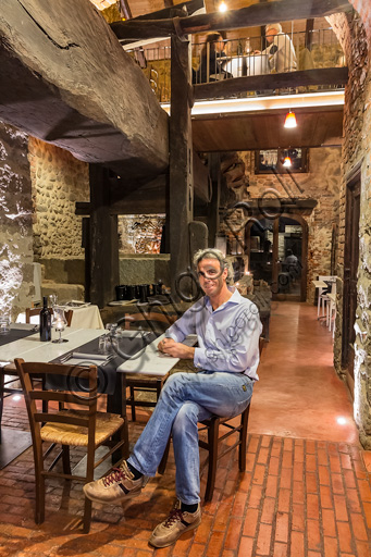 Candelo, Ricetto (fortified structure) Restaurant Il Torchio 1763:  the room with the ancient winepress and the owner Alberto Barbirato.