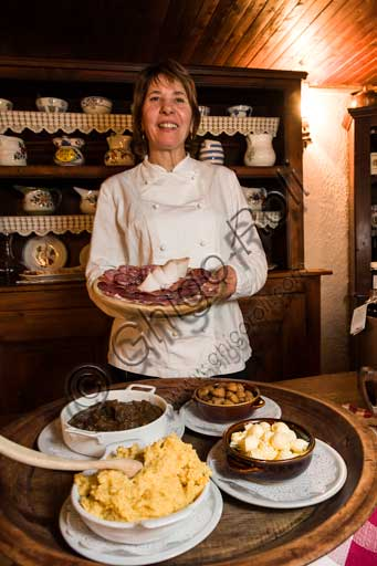 "Gressoney La Trinité, Restaurant ""La Capanna di Carla"": Susanna, cook and owner, shows a selection of cold cuts. On the table, some typical dishes such as polenta, venison stew and chestnuts."