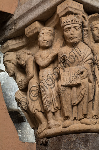 """Modena, Ghirlandina Tower, Torresani Hall: the """"Capital of the Judge"""" or """"of the Upright Judge and of the Corrupt Judge"""", work by Campionesi masters, XII - XIII century.There are three carved scenes. Detail of  one which represents the good judge crowned by an angel. In the other scene a judge is approached by a man carrying a bag and a barefoot man, pleading with his hands clasped.The inscription informs us that a crooked judge corrupted by money will give a judgment not in accordance with his conviction."""