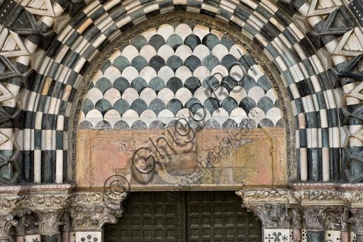 """Genova, Duomo (Cattedrale di S. Lorenzo), lato ovest, la facciata, il portale di destra: lunetta e architrave con """"Cartiglio tra angeli reggiclipeo"""" (inizi XVII secolo)."""