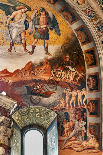 """Orvieto,  Basilica Cathedral of Santa Maria Assunta (or Duomo), the interior, Chapel Nova or St. Brizio Chapel, southern wall:  """"Call to Hell"""", fresco by Luca Signorelli, (1500 - 1502). Detail showing the Antehell, taken from Dante's description. A group of slothers has a demon bearing a white banner, while in the centre you can see Charon ready to ferry the damned, destined, lower down, to the judgment of Minos. The latter is portrayed when he commits punishment to a damned man by a demon's hair, wrapping his tail around his body as many times as the number of the group he is destined for. Further on, on the """"proscenium"""", a devil with blue flesh makes to hit a damned man by holding his hair: the crudeness of the scene interested Michelangelo, who in fact copied it."""