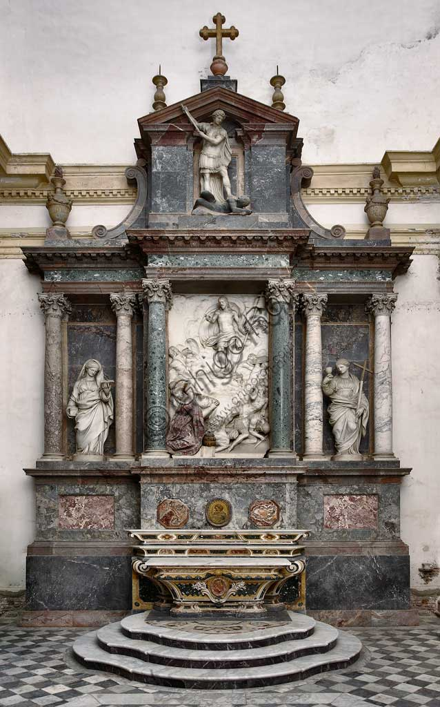 Church of Santa Croce, Mausoleum of St. Pius V: a high-relief in white marble representing  the Resurrection and Pius V in prayer. At the top, statue of St Michael defeating the devil. At the sides, the theological virtues: Faith and Charity. Based on a design by Giovanni Antonio Buzzi (1568-1571).