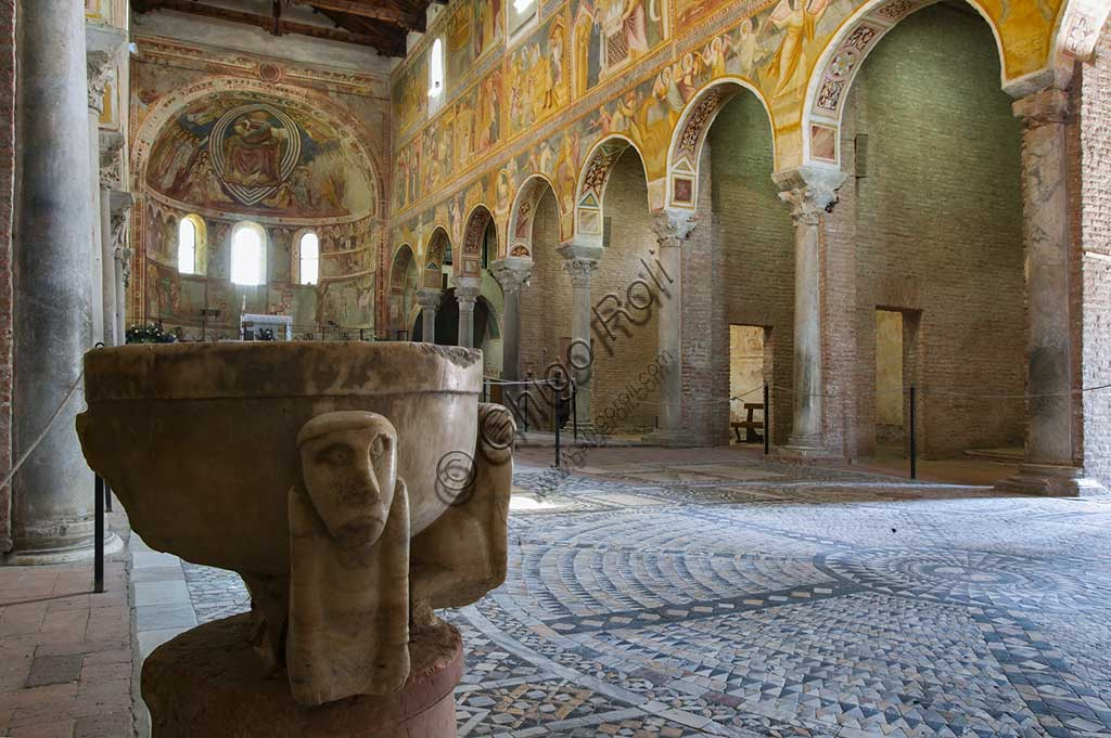 Codigoro, the Pomposa abbey: interior of the Basilica of Santa Maria. In the foreground,  the opus sectile floor (VI - XII sec) and baptismal font.