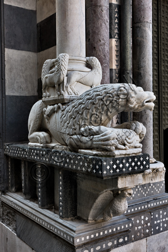 """Genova, Duomo (Cattedrale di S. Lorenzo), la facciata, lato ovest, angolo nord-ovest: base di """"colonna con leoni, leonesse e leone stiloforo"""" e mensola con """"Aquila di S. Giovanni evangelista"""", di bottega di Benedetto Antelami, 1200 circa."""