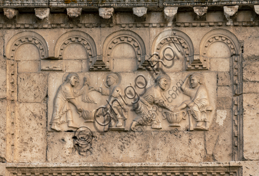 """Spoleto, St. Peter's Church, the façade ( It is characterized by Romanesque reliefs (XII century), detail of one of the five bas-reliefs to the right of the main portal: """" Christ washing St. Peter's feet""""."""