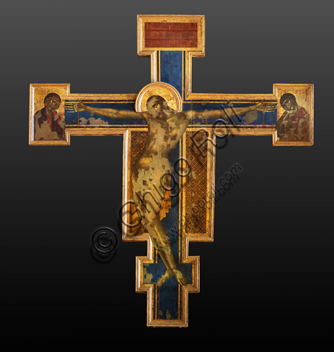 "Basilica of the Holy Cross: Crucifix"", (1272-80) by Cimabue, tempera on wood. On the sides of Christ on the cross, the Madonna and St. John the Evangelist.The cross bears the iconography of the Christus patiens, that is, a dying Christ on the cross, with his eyes closed, his head resting on his shoulder and his body arched to the left."