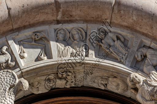 Foligno, Cathedral of  St. Feliciano, the façade:  the entrance door. Detail of the frieze of  the portal. The central portal, work of the masters Rodolfo and Binello, shows a solar disk in the lunette, in which there is the inscription with the date 1201, the year of completion of the facade; in the inner façade of the jambs there are then the reliefs with the Emperor Otto IV of Brunswick and Pope Innocent III, while the inner circle of the arch is decorated by the symbols of the evangelists and the Signs of the zodiac; in the outer circle a band of cosmatesque mosaics. The carved wooden portal was made in 1620.