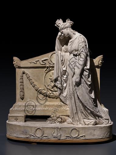 """""""Modello del monumento a Vittorio Alfieri"""", 1806, di Antonio Canova (1757 - 1822), gesso.  Sopra un alto basamento ovale, sormontato da un ulteriore gradone, decorato da festoni e da un'epigrafe dedicatoria, si erge il sarcofago che porta scolpito sul frontone il ritratto in profilo del poeta entro un medaglione con la scritta «VICTORIVS ALFERIVS ASTENSIS». La figura dolente è allegoria dell'Italia e piange la perdita di uno dei suoi più stimati figli, nell'atteggiamento composto e solenne di un'antica matrona."""