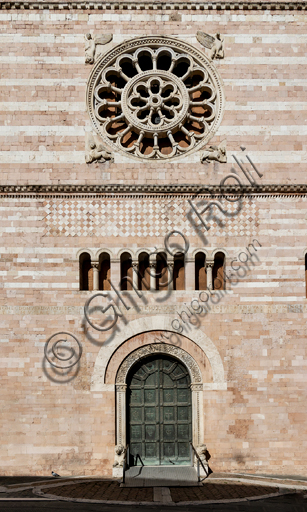 Foligno, Cathedral of  St. Feliciano, the façade: detail of the entrance door and the romanesque rose. The central portal, work of the masters Rodolfo and Binello, shows a solar disk in the lunette, in which there is the inscription with the date 1201, the year of completion of the facade; in the inner façade of the jambs there are then the reliefs with the Emperor Otto IV of Brunswick and Pope Innocent III, while the inner circle of the arch is decorated by the symbols of the evangelists and the Signs of the zodiac; in the outer circle a band of cosmatesque mosaics. The carved wooden portal was made in 1620.