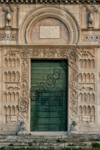 Spoleto, St. Peter's Church: the façade. It is characterized by Romanesque reliefs (XII century). Detail of the main portal. This portal is surmounted by a horseshoe lunette, surrounded by two eagles and Cosmatesque decorations. On the sides of the jambs there are four orders of decorative arches on columns with a background of flowers, stylized animals and geometric figures, interspersed two by two by symbolic sculptures in full relief (the worker with the oxen and the dog, the deer suckling her newly born and devours a snake, the peacock pecking grapes).