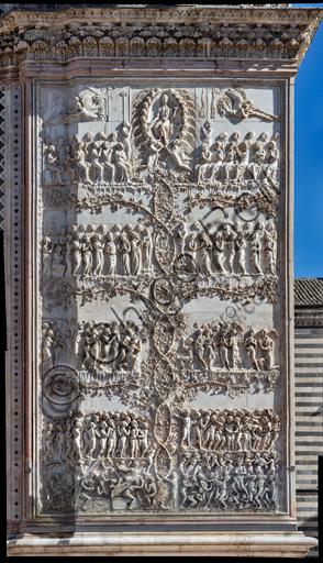 Orvieto, Basilica Cattedrale di Santa Maria Assunta (o Duomo): la facciata, iniziata alla fine del XIII secolo. Particolare del rivestimento dei quattro pilastri delle porte. Si tratta di lastree marmoree con bassorilievi eseguite tra il 1320 e il 1330 da Lorenzo Maitani con l'aiuto di maestranze senesi e pisane.Rappresentazione del Giudizio Universale in scene divise da rami di vite: Cristo giudice tra angeli, profeti, apostoli, Maria, il Battista, gli strumenti della passione e gli angeli che chiamano i morti al Giudizio; Gli Eletti condotti alla beatitudine celeste; La divisione degli eletti dai reprobi; La Resurrezione dei morti e la cacciata dei reprobi nell'Inferno.