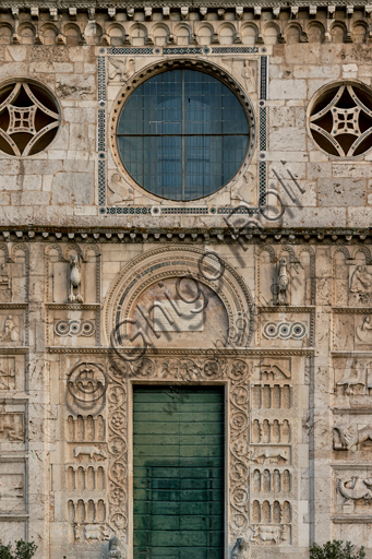 Spoleto, St. Peter's Church: the façade. It is characterized by Romanesque reliefs (XII century). Detail of the middle part with the central oculus (which is framed by a Cosmatesque decoration and surrounded by symbols of the Evangelists) and the main portal. This portal is surmounted by a horseshoe lunette, surrounded by two eagles and Cosmatesque decorations. On the sides of the jambs there are four orders of decorative arches on columns with a background of flowers, stylized animals and geometric figures, interspersed two by two by symbolic sculptures in full relief (the worker with the oxen and the dog, the deer suckling her newly born and devours a snake, the peacock pecking grapes).