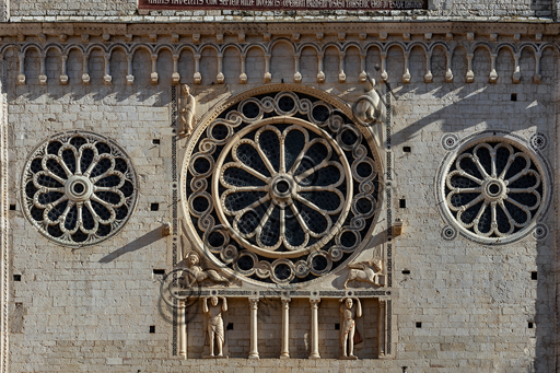 Spoleto, the Duomo (Cathedral of S. Maria Assunta): detail of the upper part of the façade with some roses. The central rose is surrounded by the symbols of the Evangelist and at its basis there is a blind gallery with two telamons.