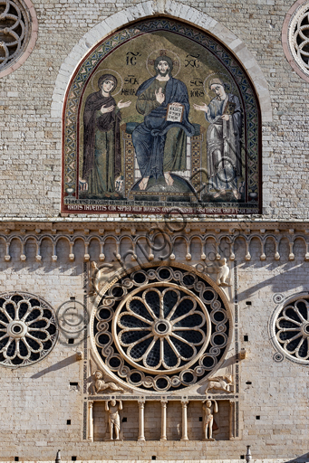 """Spoleto, the Duomo (Cathedral of S. Maria Assunta): detail of the upper part of the façade with some roses and  a blind gallery with two telamons. In the centrale niche, the mosaic """"Enthroned Christ between the Virgin Mary and St John the evangelist"""", by Solsterno (1207)."""