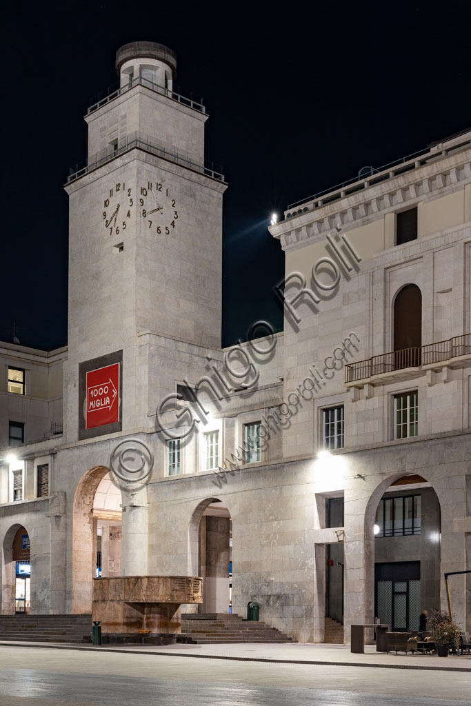Brescia: night view of piazza della Vittoria (square built between 1927 and 1932) designed by the architect and urban planner Marcello Piacentini. Detail of the Tower of the Revolution and of the Arengario, pulpit in red stone of Tolmezzo decorated with bas-reliefs depicting scenes of the history of Brescia, by Antonio Maraini (1932).