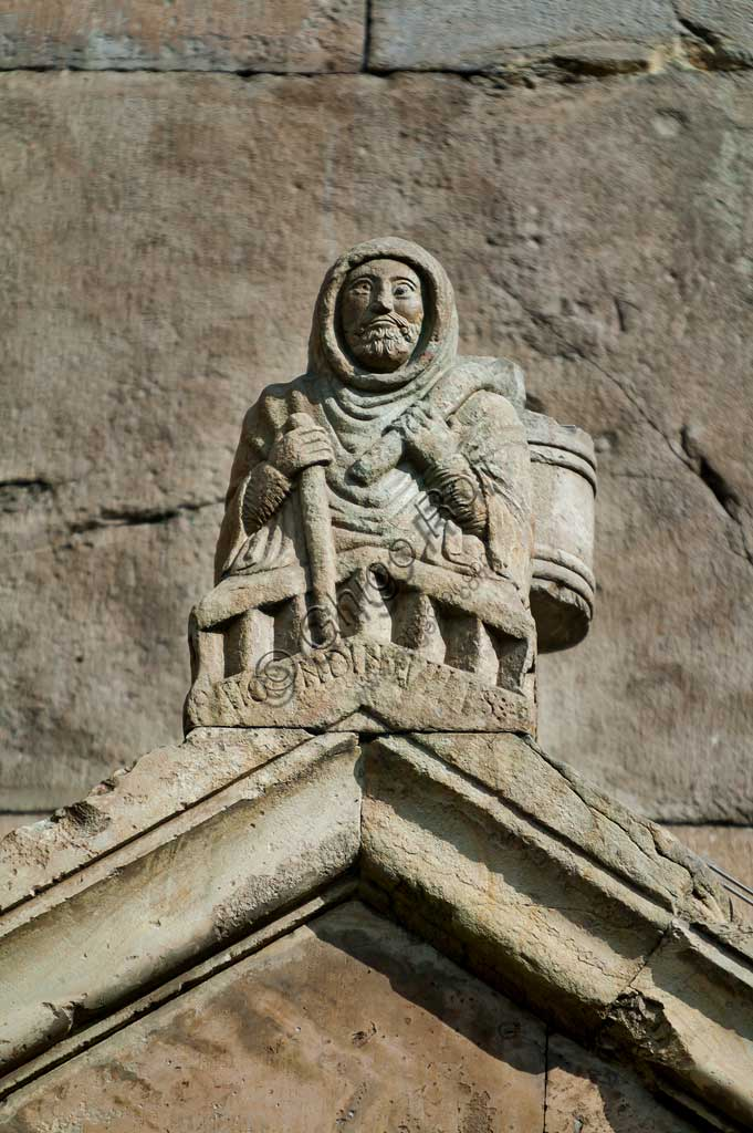 Fidenza, Duomo (St. Donnino Cathedral), Façade, the acroterion of the right portal: the bas-relief with the figure of Raimondinus vilis.A writing identifies him as Raimondinus vilis (the humble Raimondino) on whose identity there are more doubts than certainties. Several hypotheses qualify him as: a poor pilgrim died in Borgo San Donnino; a man who became a symbol of the poor people and contributed to the church's construction; Saint Raimondino da Piacenza, a holy pilgrim. Work by Benedetto Antelami and his workshop.
