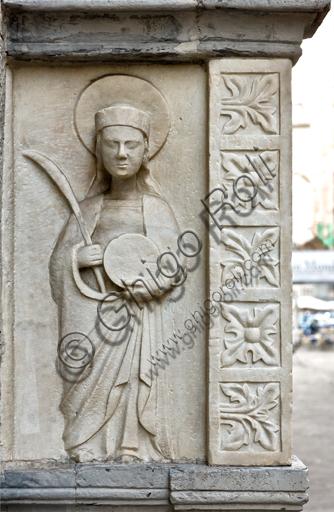 """Genova, Duomo (Cattedrale di S. Lorenzo), fianco sud: """"tomba pensile di Antonio Grimaldi - particolare con figura di pellegrino che tiene in mano la palma e la ruota del martirio"""", (post 1402)."""