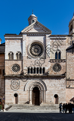 Foligno, the Cathedral of  St. Feliciano: the façade with the entrance door and the roses. The central portal, work of the masters Rodolfo and Binello, shows a solar disk in the lunette, in which there is the inscription with the date 1201, the year of completion of the facade; in the inner façade of the jambs there are then the reliefs with the Emperor Otto IV of Brunswick and Pope Innocent III, while the inner circle of the arch is decorated by the symbols of the evangelists and the Signs of the zodiac; in the outer circle a band of cosmatesque mosaics. The carved wooden portal was made in 1620.