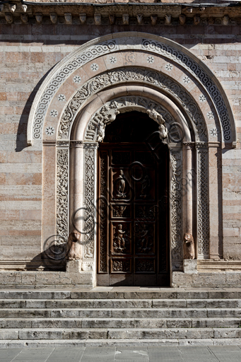 Foligno, Cathedral of  St. Feliciano, the façade:  the entrance door. The central portal, work of the masters Rodolfo and Binello, shows a solar disk in the lunette, in which there is the inscription with the date 1201, the year of completion of the facade; in the inner façade of the jambs there are then the reliefs with the Emperor Otto IV of Brunswick and Pope Innocent III, while the inner circle of the arch is decorated by the symbols of the evangelists and the Signs of the zodiac; in the outer circle a band of cosmatesque mosaics. The carved wooden portal was made in 1620.