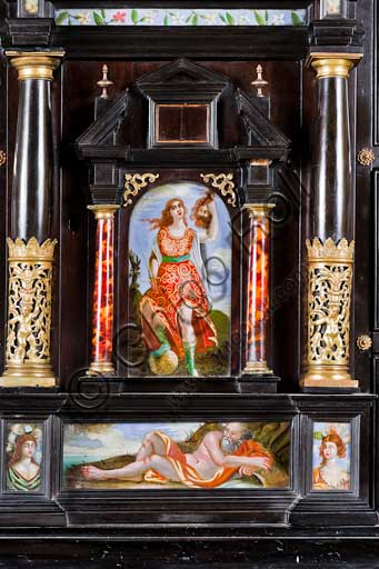 Palermo, The Royal Palace or Palazzo dei Normanni (Palace of the Normans), The Royal Apartment, The Monetiere Room (next to the Chinese Room): the Monetiere, i.e. the wooden cabinet with an ebony veneer, and inlays in tortoise, red lacquers and gilded bronze. Painted glass panels with biblical, mythological and allegorical scenes. Sicilian cabinetmakers, XVII century. Detail with Judith and Holofernes.