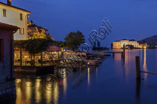 Isola Pescatori: the lakefront with a pier of a restaurant and some boats. In the background, night view of Isola Bella with the illuminated Borromeo Palace.