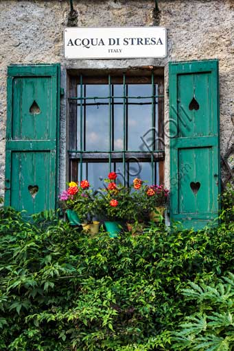 Isola Pescatori: view of the village with window, flowers and sign.