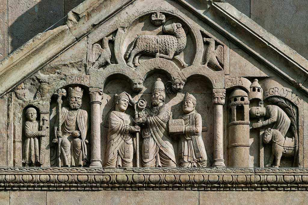 "Fidenza, Duomo (St. Donnino Cathedral), Façade, the porch pediment   of the left portal.Frrom left to right: ""The emperor Charlemagne, with a warrior on his right"";""Pope Adrian II who hands the mitre and the croiser (symbols of episcopal dignity) to the archpriest of San Donnino""; ""The miracle of the sick recovered by Domninus of Fidenza"". Work by Benedetto Antelami and his workshop."