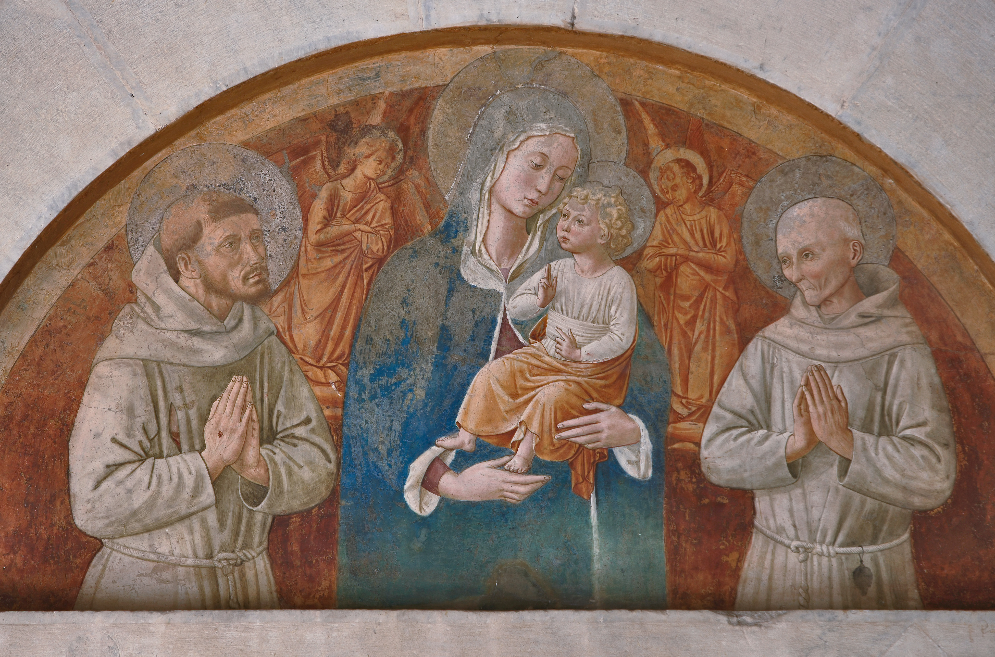 "Montefalco, Church of San Fortunato, lunette above the portal: ""Madonna and Child with Saints Francis and Bernardino"", fresco by Benozzo Gozzoli."