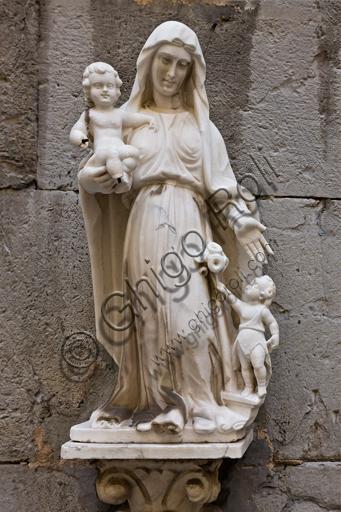 """Genova, Duomo (Cattedrale di S. Lorenzo), fianco sud, sezione tra il campanile e il portale di S. Gottardo: """"Madonna con Bambino e S. Giovannino che porge dei fiori"""" (secondo quarto del XVII secolo)."""