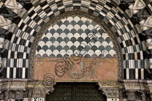 """Genova, Duomo (Cattedrale di S. Lorenzo), lato ovest, la facciata, il portale di destra: lunetta e architrave con """"Madonna con Bambino tra angeli reggiclipeo"""" (inizi XVII secolo)."""